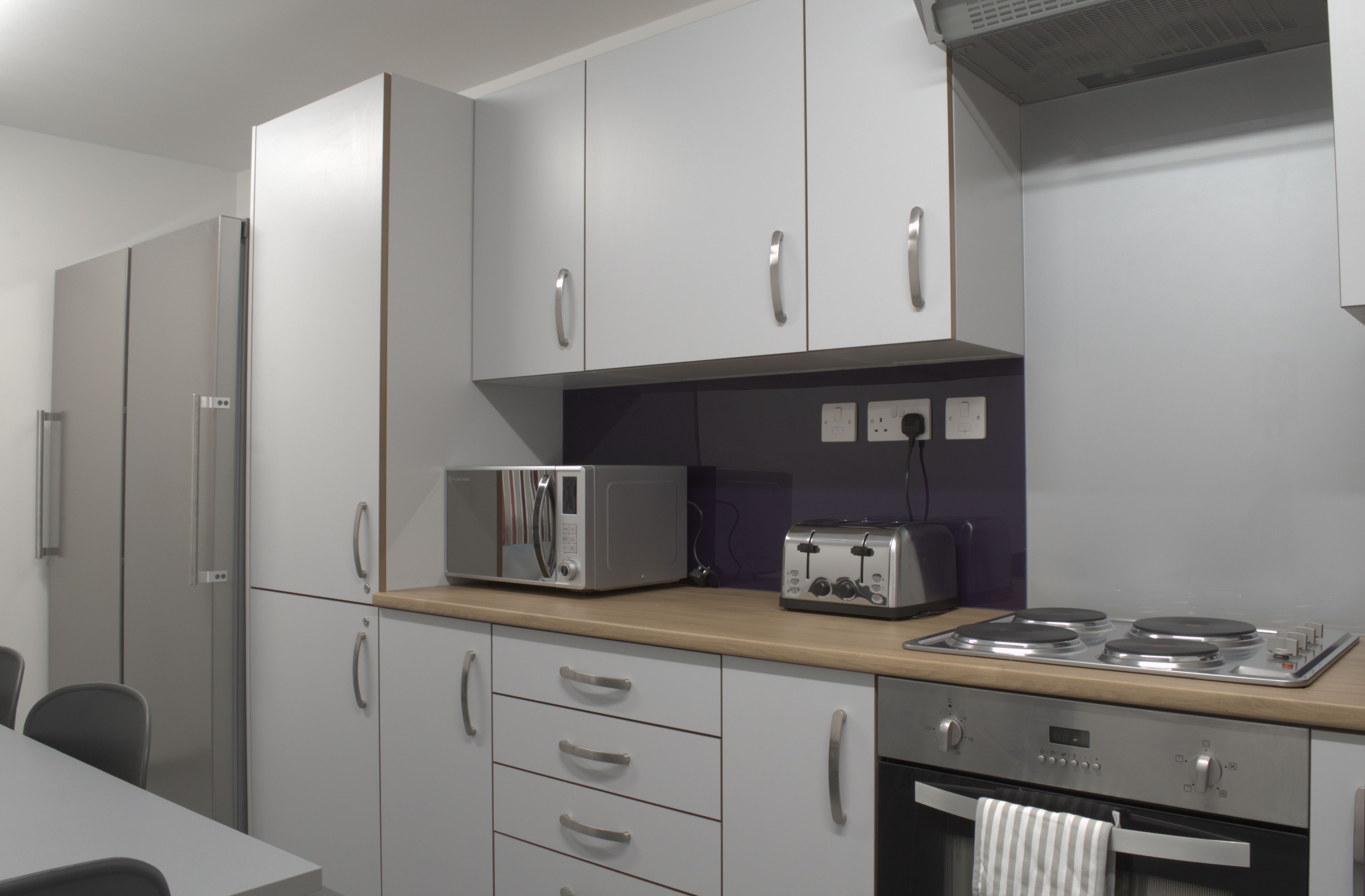 A kitchen with grey and purple units, a hob, oven, toaster, microwave and fridge.