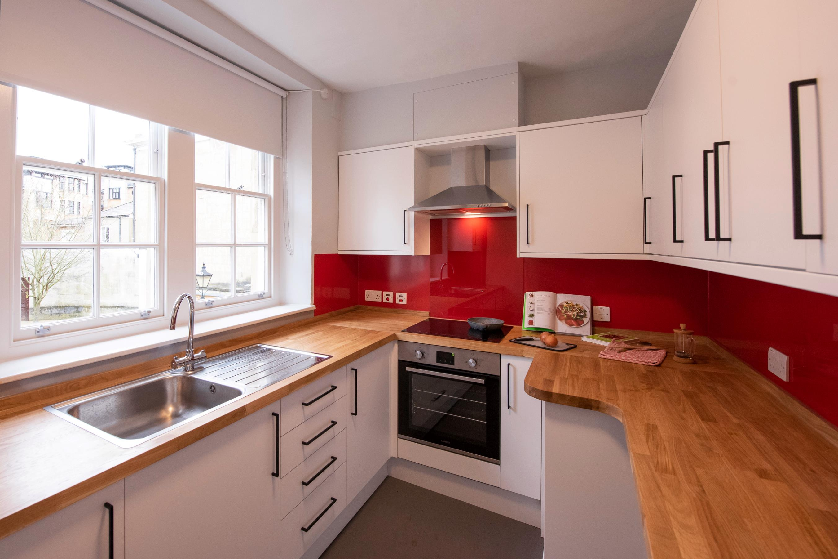 View of a square kitchen, with white units on three sides including a sink, hob and oven. There is a window and red splash-backs.