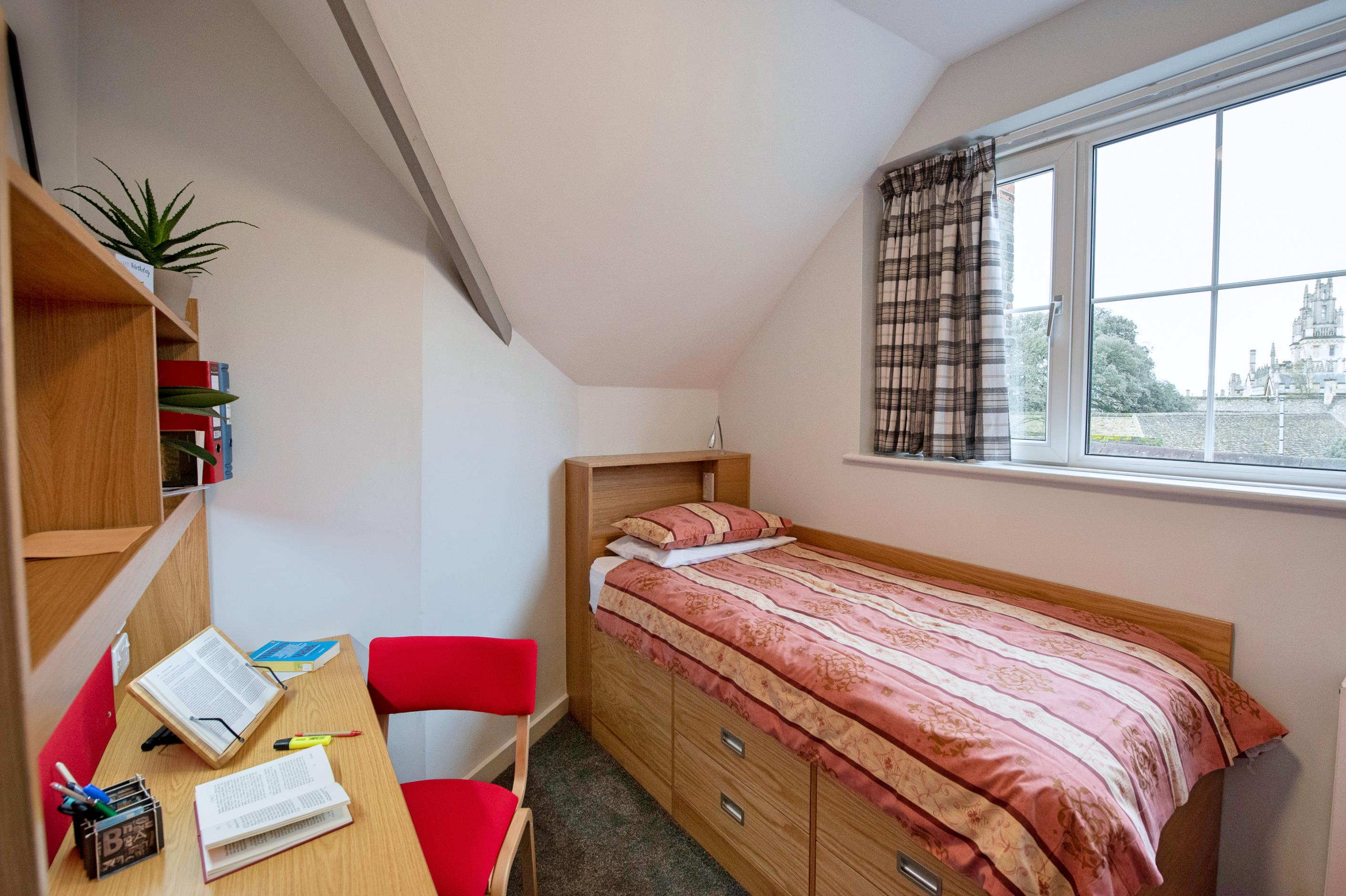 A student bedroom with a dormer ceiling line. There is a bed and desk and a window.