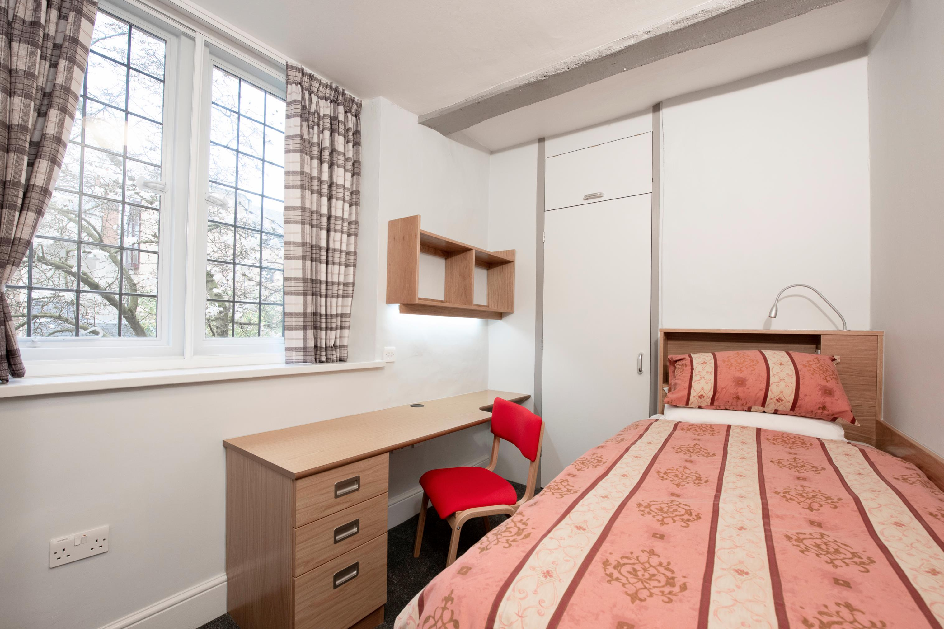 A student bedroom featuring a bed, desk, shelves and leaded widow.