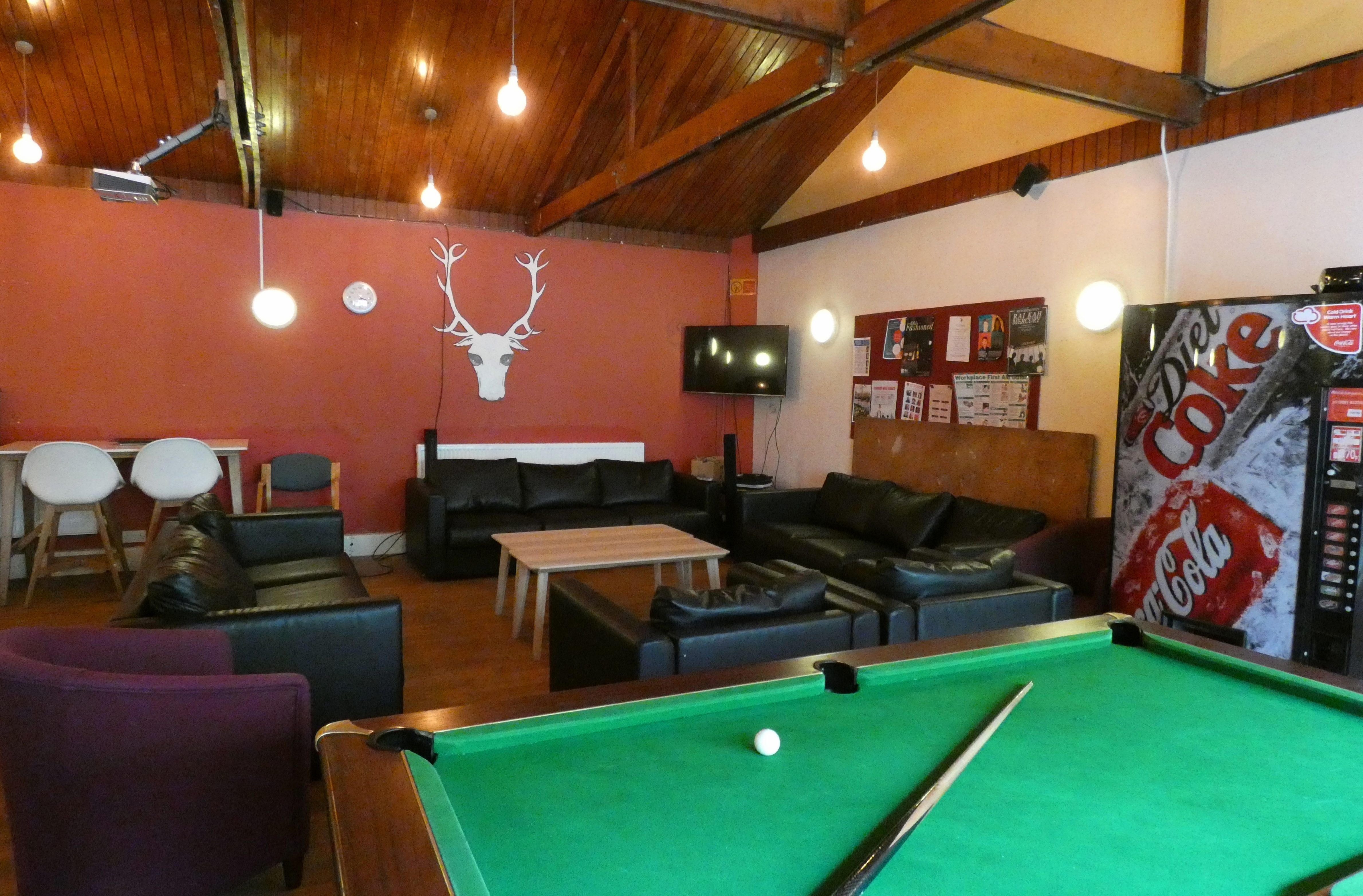 A brightly lit room with sofas, pool table and vending machine