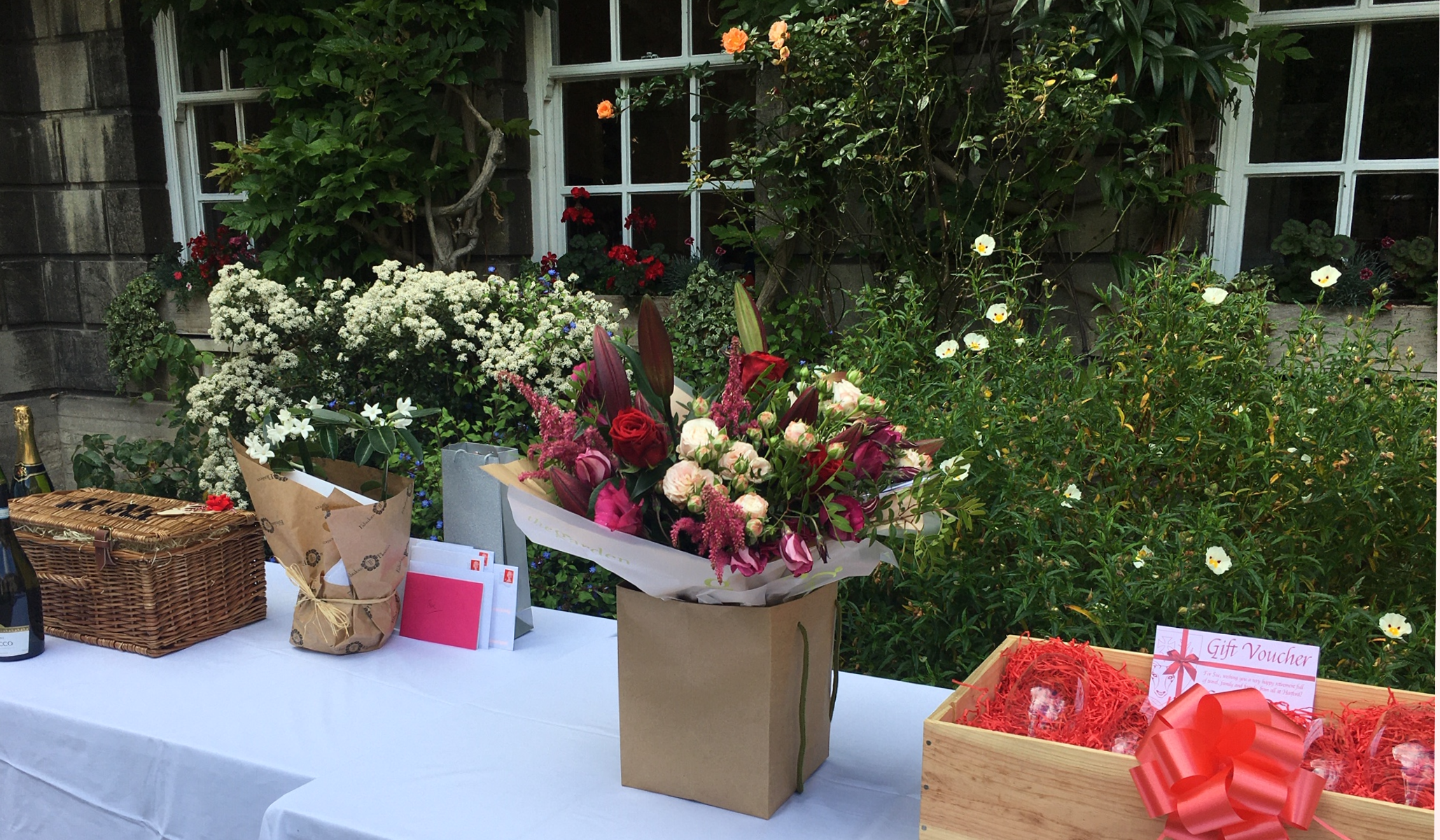 Table with gifts including a bunch of flowers and hampers