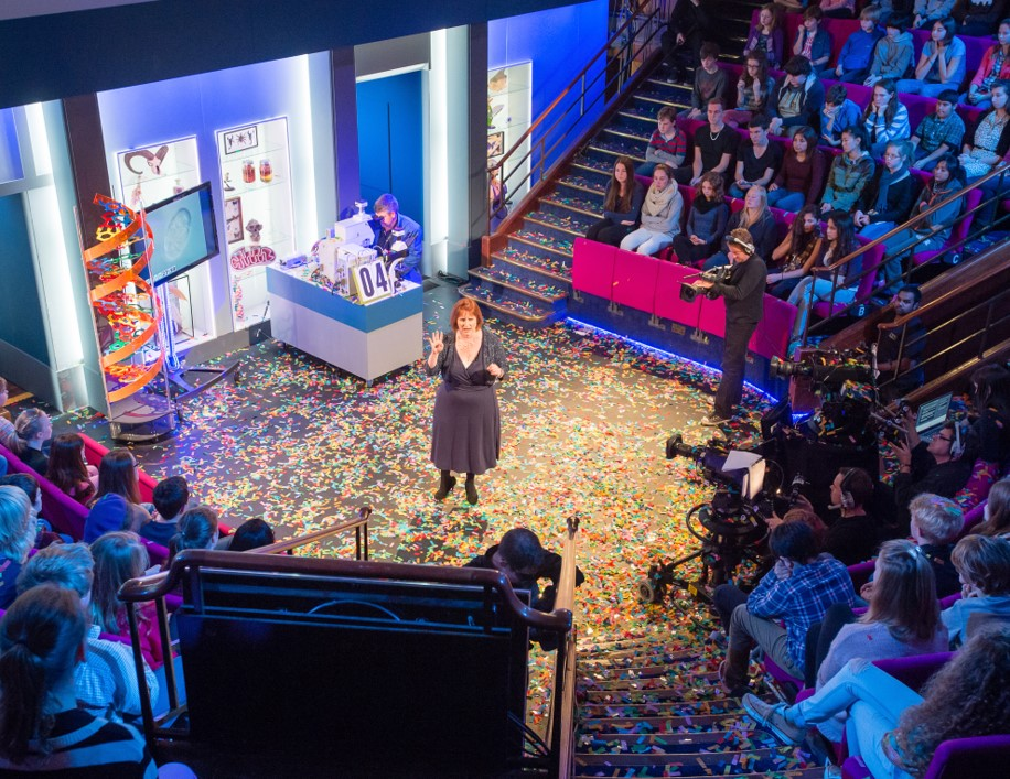High angle shot of Alison Woollard delivering a lecture. There is confetti on the floor and the audience is ranged round her iin a semi-circle.